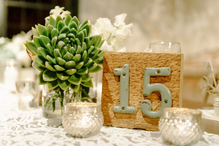 Large wooden blocks had cast iron numbers depicted on the front, marking tables for friends and family to find their seats. In addition to the number, each dining table had votive candles and a succulent decorating its surface.
