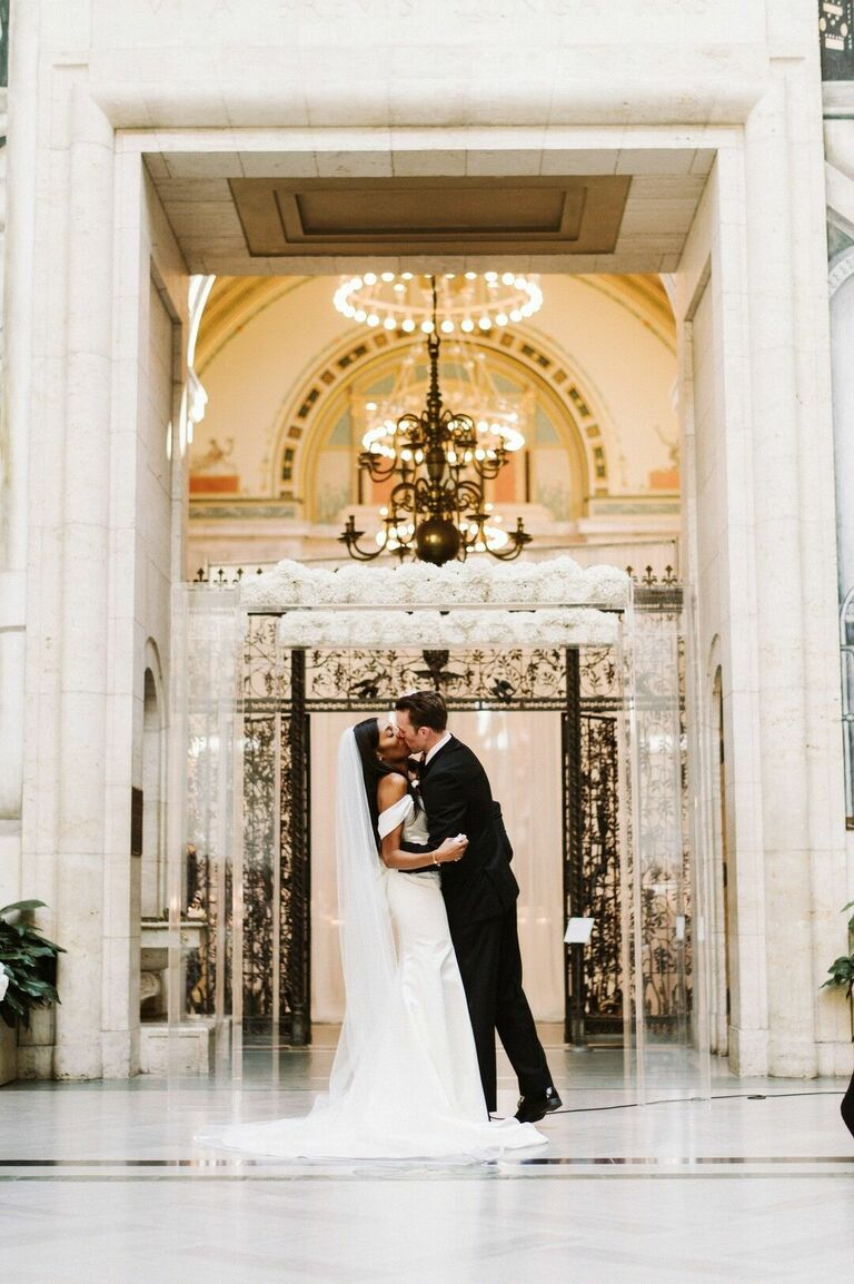Ceremony first kiss in front of acrylic arch with white flowers