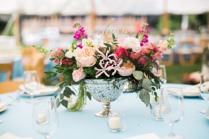 A tented reception followed the alfresco ceremony, where vibrant color and fresh florals ruled supreme. Pale blue table linens and arrangements of garden roses, stock, eucalyptus and more cascading from antiqued silver vases filled the expansive space with energy and life.