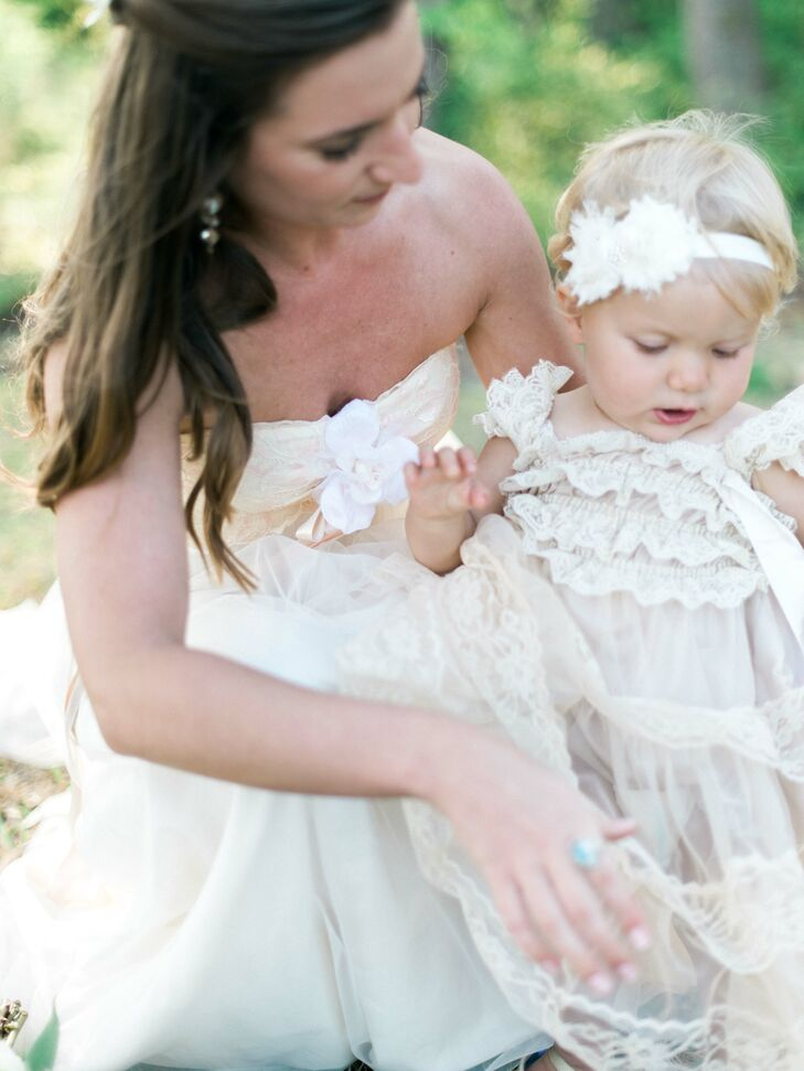 "Ashley and her daughter, Marlowe, dressed in a pink dress with lace detail and matching headpiece, share a sweet moment before the wedding begins. It was important to Ashley to keep things family oriented, so her ""something blue"" was a topaz ring that had belonged to her late mother."