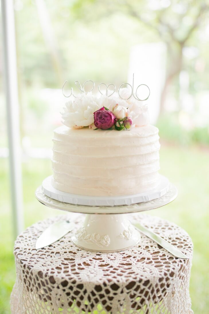 "The single-tier, strawberry- champagne-flavored wedding cake was simply decorated with fresh-cut flowers and a ""We Do"" topper. Homemade sugar cookies were also on offer at the reception."
