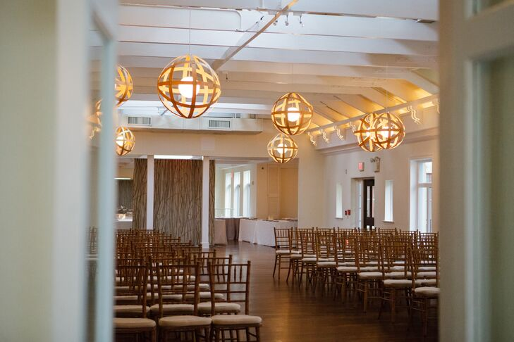 """We fell in love with the beautiful rustic elegance of Pomme,"" Lily says. ""We knew it wouldn't take much to transform it into the romantic candlelit room we imagined."" Lily and Aaron chose decor that only enhanced the space. Rows of gold chiavari chairs faced a chic vintage fireplace for the ceremony."
