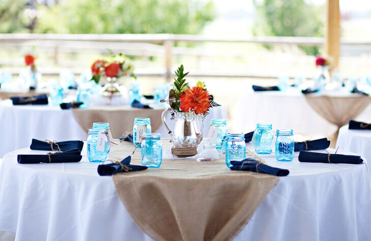 White tablecloths and burlap runners covered dining tables at the reception, with blue mason jars at each seat. Antique silver teapots filled with colorful blooms decorated the middle of dining tables, adding a pop of color to the display.