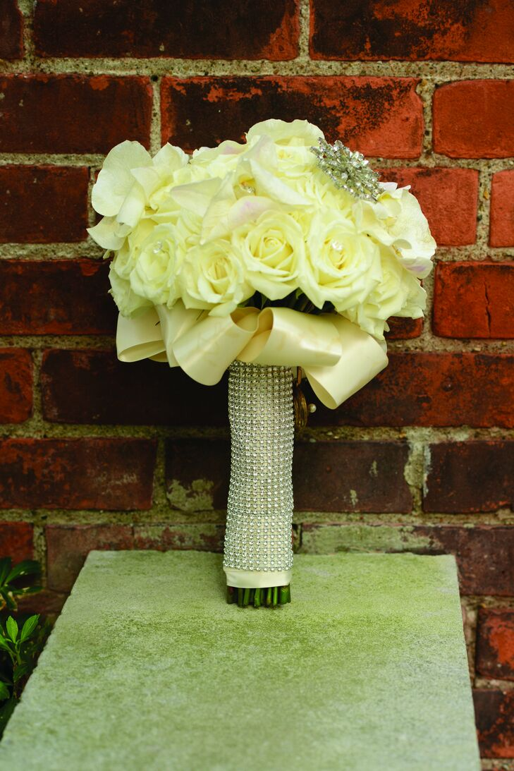 """Whitney's white rose bouquet was adorned with a crystal brooch and wrapped in crystal-encrusted ribbon for a """"bling"""" effect."""
