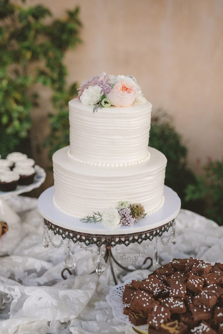 A simple two-tier rough-frosted cake reflected the wedding's naturalistic, relaxed themes. Other treats such as brownies and cupcakes were set upon the vintage lace-covered dessert table.
