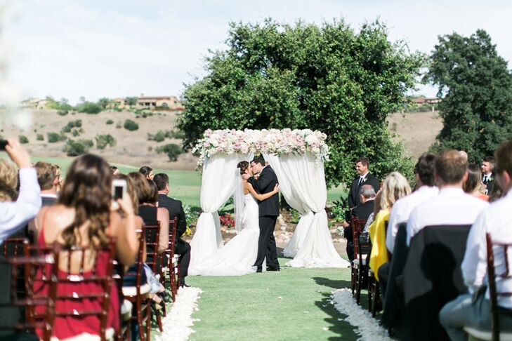 "As 120 guests looked on, Bree and Greg shared their first kiss under a fabric-draped wedding arch topped with a rose garland on the grounds of Santaluz Club in San Diego, California. ""I have always wanted a soft and romantic garden wedding,"" Bree says."