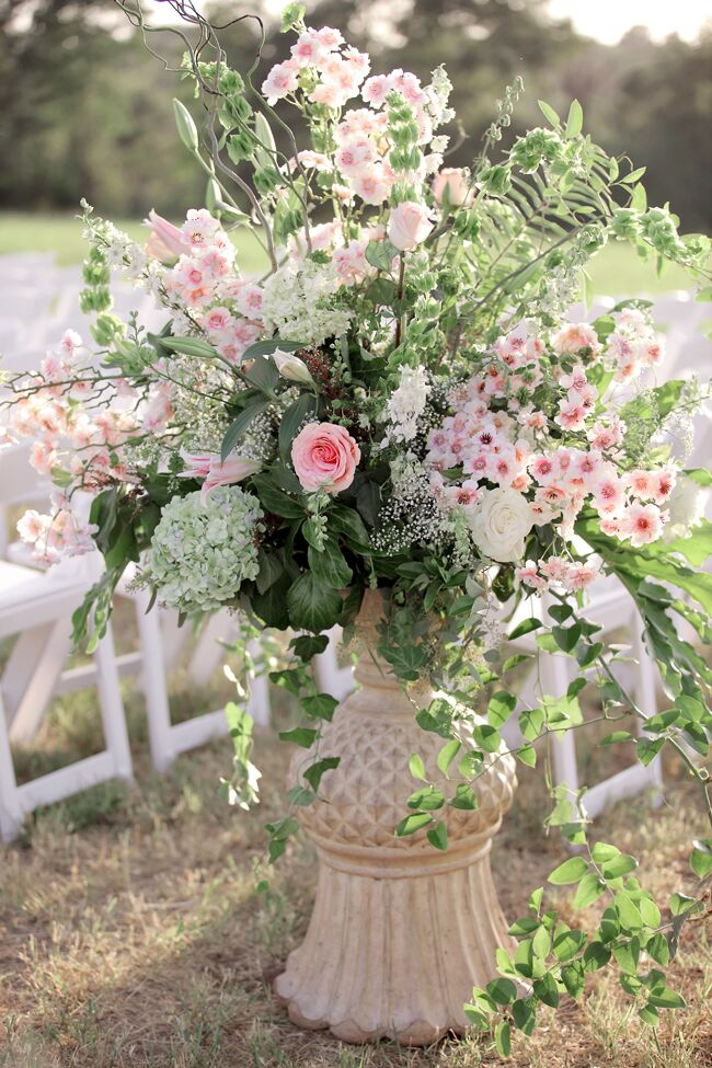 Bursting flower arrangements of greenery with  roses, hydrangeas and Bells of Ireland in decorative urns marked the aisle entrance at Anna and Adler's outdoor ceremony at Enoch's Stomp Vineyard and Winery in Harleton, Texas.