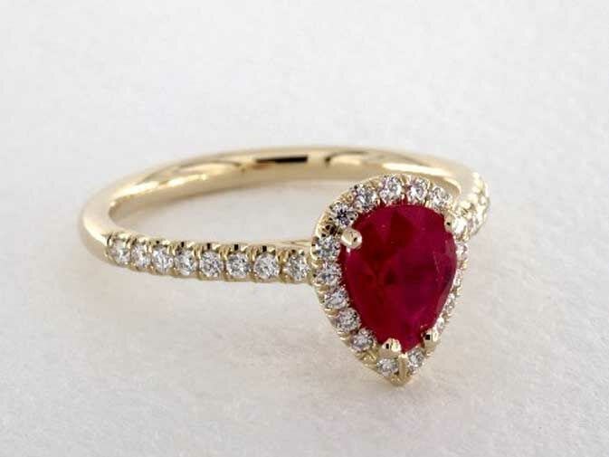 Ruby pear-shaped engagement ring with diamond halo and diamond band