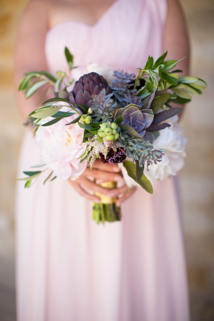 Bridesmaids carried bouquets of green and purple flowers down the aisle, including succulents, bay leaves and blueberries.