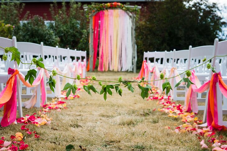 The ceremony was a bright, outdoor celebration just outside the barn at Red Barn Studios. A leafy garland blocked guests from waking down the center aisle before the bride made her own way, while loose orange and pink petals lined the rustic grass aisle and the focal point was an ombre pink and orange birch tree arbor decorated with garlands, flowers and streamers.
