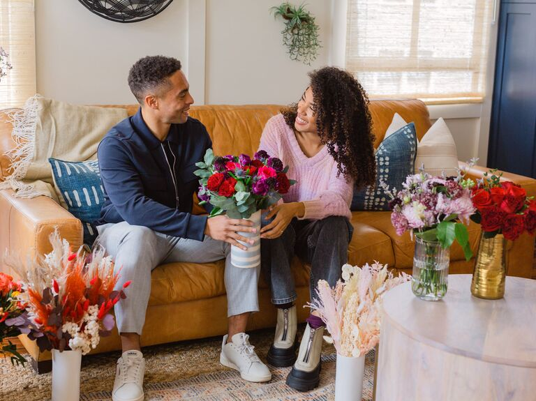 Couple sitting on sofa exchanging a vase of flowers