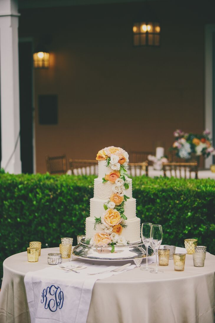 Four round tiers were iced in white and decorate with fresh peach and white flowers cascading downward with greenery. To ensure enough cake for all the guests, backup sheet cakes of banana chocolate chip and lemon with buttercream icing were added to the dessert table.