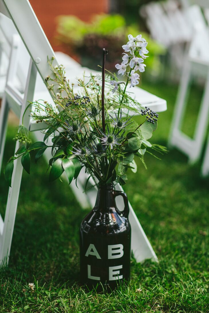 Growlers from local breweries doubled as vases for the wildflower arrangements that lined the ceremony aisle.