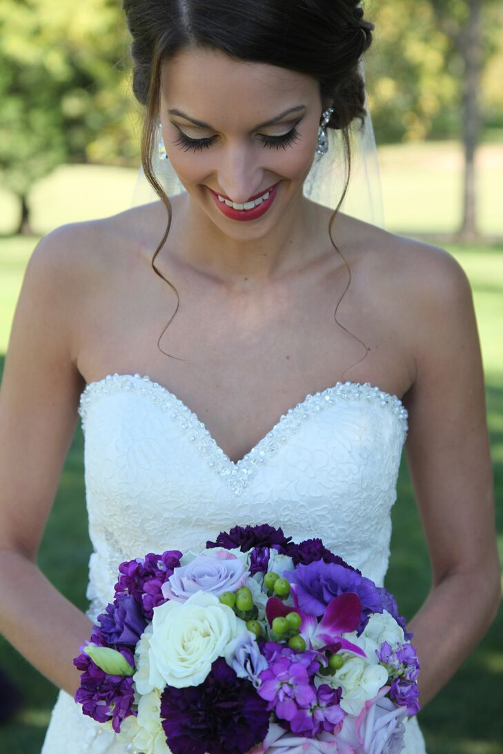 A bright purple bouquet filled with roses, lisianthuses, stock, orchids and hypericum berries added a pop of bright color to Katie's bridal look.