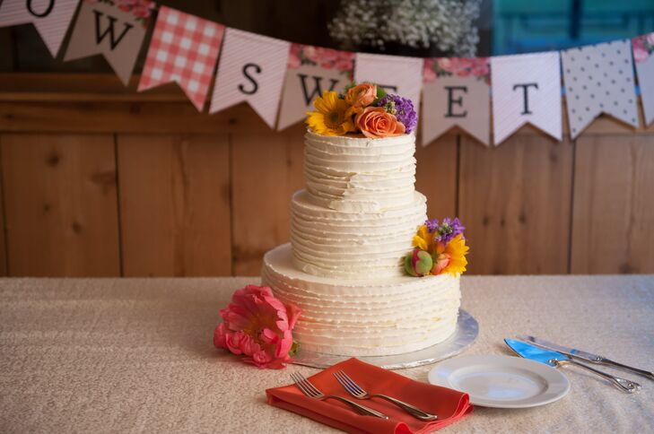 Katie and Haydn enjoyed a three-tier white ruffled buttercream wedding cake topped with fresh daisies and roses.