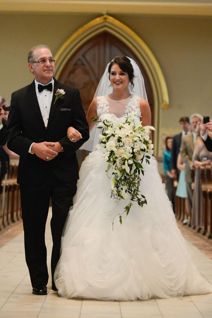 "Amanda carried a cascading bouquet of all-white spray roses, mini calla lilies, sweet peas and freesia with pearl-studded stephanotis and whimsical jasmine vines. She held on to a bouquet wrap of lace from her mother's wedding dress and her grandmother's rosary as she walked down the aisle to a live performance of ""Prince of Denmark's March."""