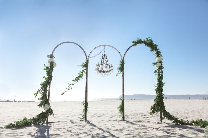 """""""The altar was a brass frame that my planner found. and it was asymmetrically draped with greenery with a vintage chandelier hung in the middle,"""" Bayley says."""