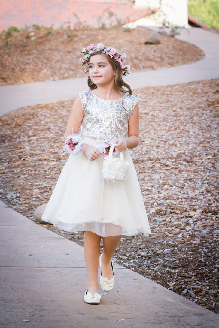 The flower girl walked down the aisle wearing a dress with a silver sparkly top that flared out into a knee-length tulle skirt. A pastel-colored flower crown was placed on top of her down hairstyle, and she held a small, white basket filled with petals.