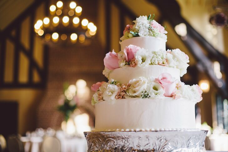 The couple's traditional white cake was adorned with pink and white roses, hydrangeas and wax flowers on each tier.