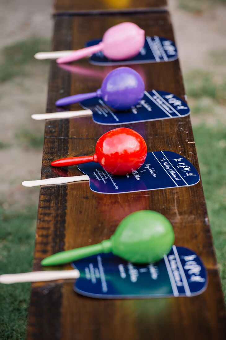 Before they even got to the reception, guests were encouraged to have some fun. Every seat had a navy (to keep away the heat) and a bright-colored maraca to shake during the couple's first kiss.