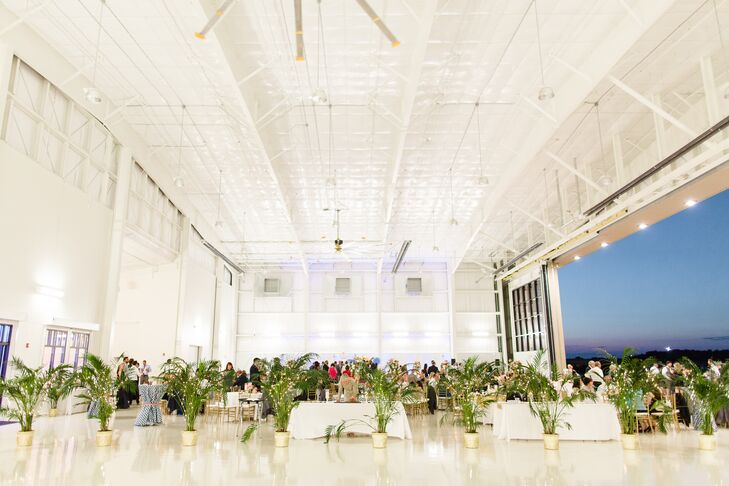 Kelsey wanted to add some color and sparkle to the all-white airplane hangar. She separated the ceremony area from the reception with palms and ferns for greenery, which she filled with fairy lights. The hangar turned into a room with a view when the doors opened to reveal the beautiful Georgia sunset and fresh evening air.