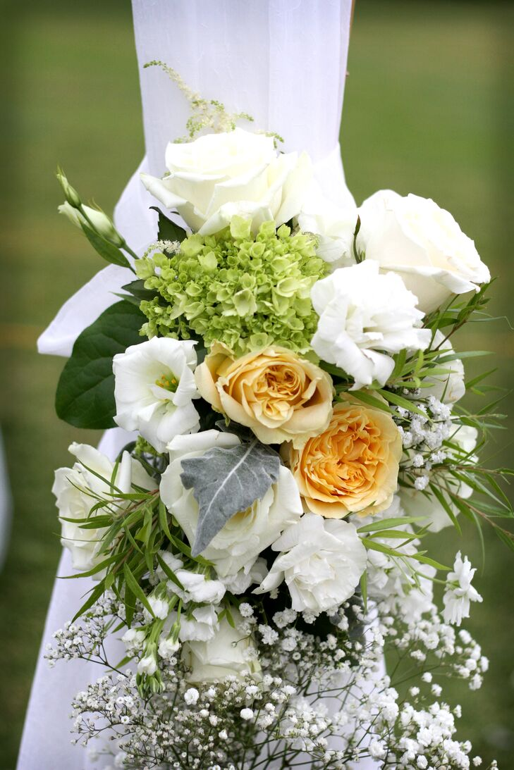 The couple accented their wedding with arrangements of white roses, green hydrangea, white lisianthus and pale yellow garden roses.