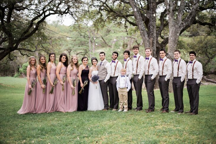 The bridesmaids wore flowing floor-length tulle dresses in a dark blush. The maid of honor wore a dark purple dress to match the groomsmen's bow ties. All the dresses were one-shouldered and braided down the back for an unexpected, elegant twist.