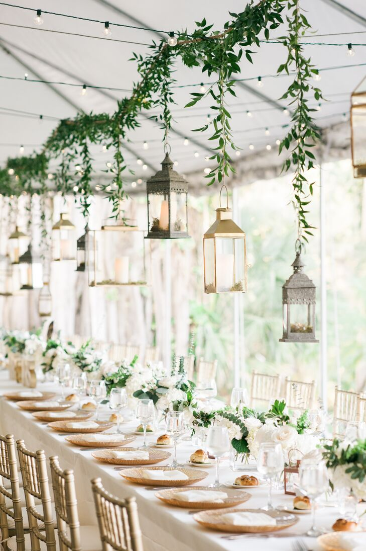 Ashleigh and Alex hosted their reception in an open tent in front of the historic Bonnet House Museum and Gardens in Fort Lauderdale, Florida. Hanging over the long tables were centerpieces of different metals, brass and glass wrapped in verdant garlands.