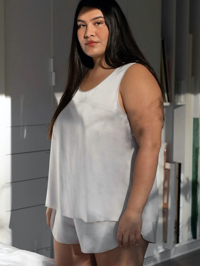 Plus-size model wearing white silk tank and shorts set