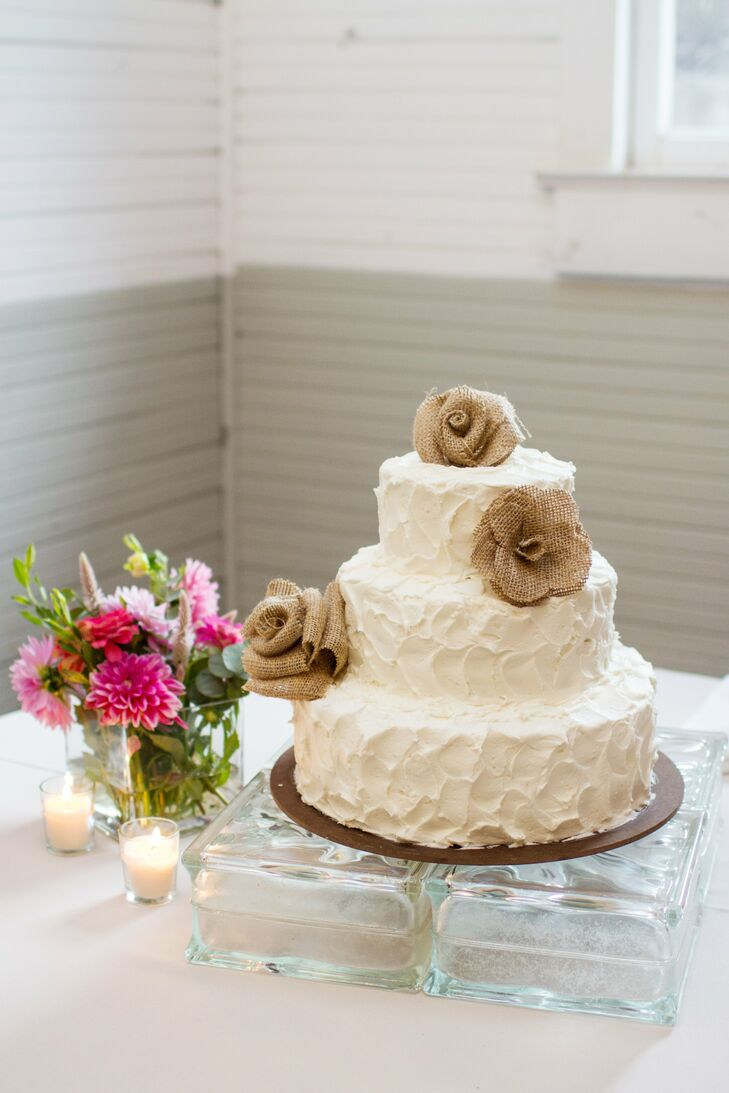 The couple kept with their burlap theme in their dessert display by topping their rustic, unevenly frosted cake with burlap rosettes.