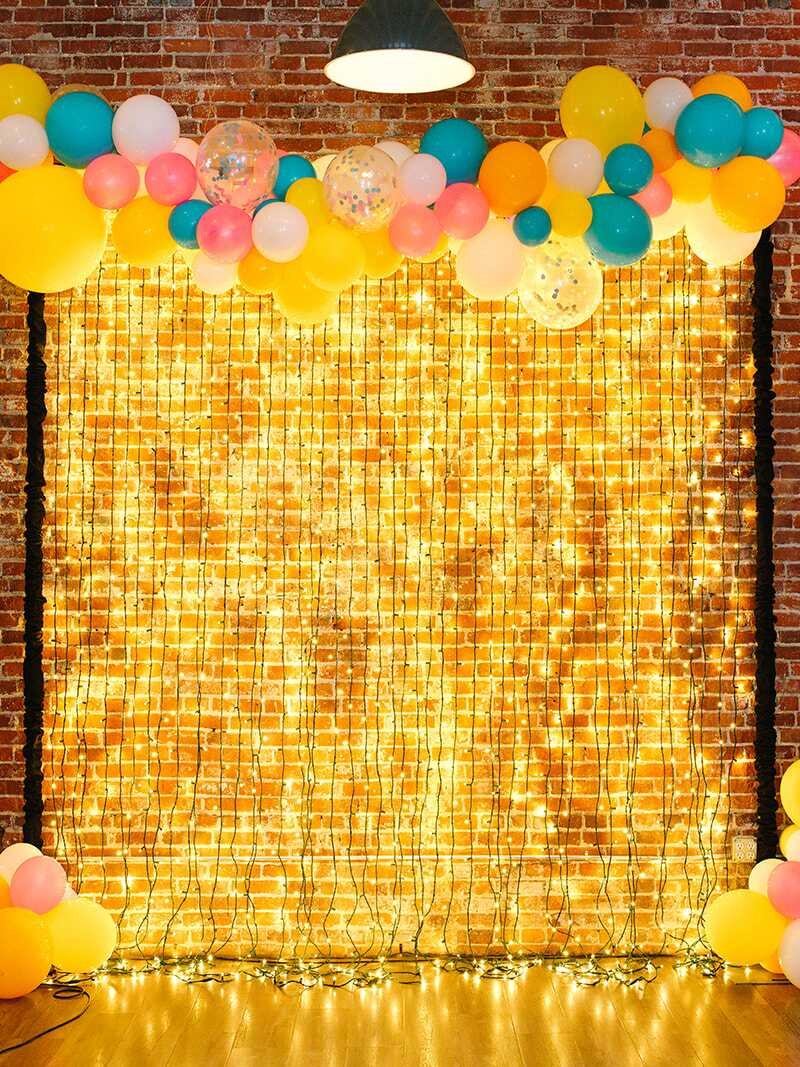 Teal and yellow balloon garland decorating a photo backdrop of string lights
