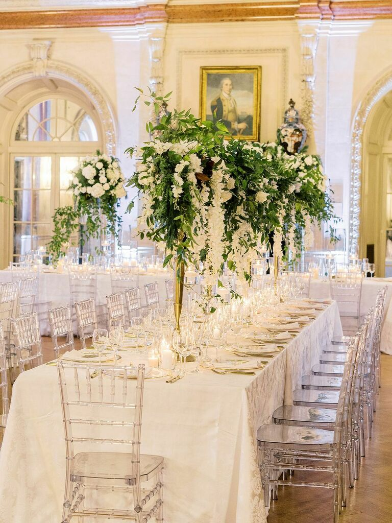 Romantic white reception decor with tall greenery centerpieces