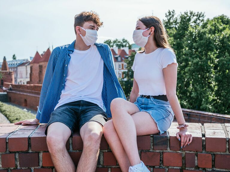 Young couple wearing masks on outdoor date amid coronavirus pandemic