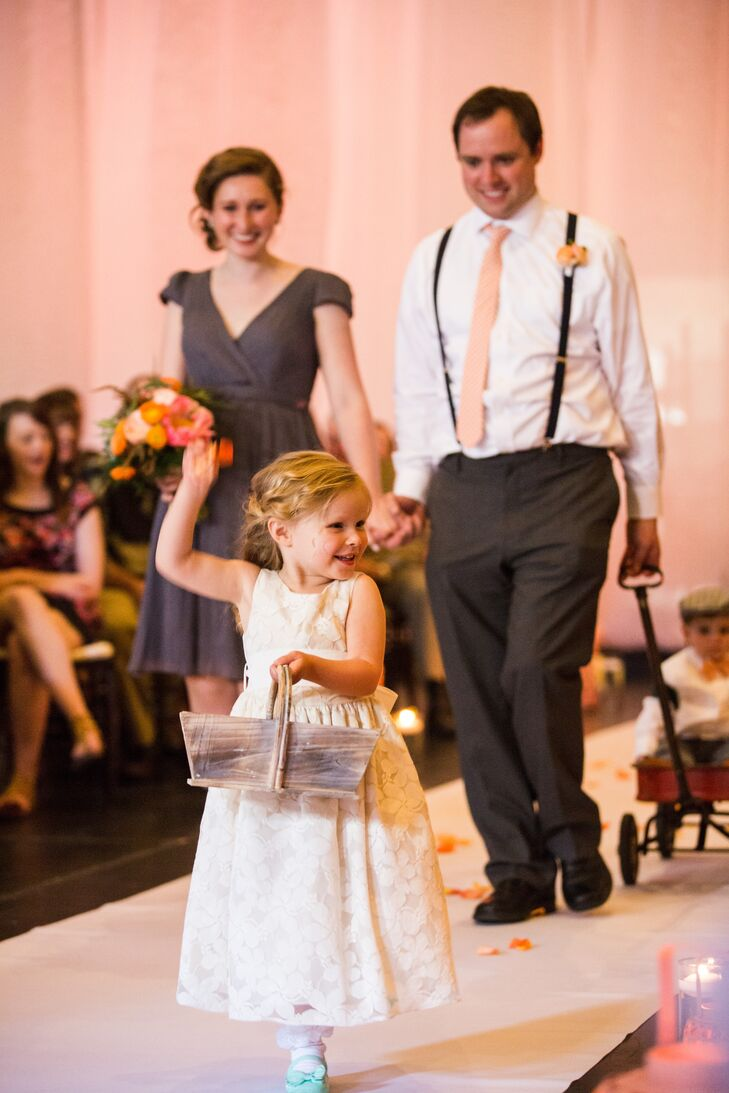 The flower girl, Effie, walked down the aisle wearing a super-cute white dress. She carried a wooden basket filled with pink and orange rose petals, which she threw as she walked down the aisle.