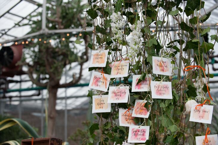 White escort cards with a pink watercolor design hung from a large plant at the entrance to the reception site.