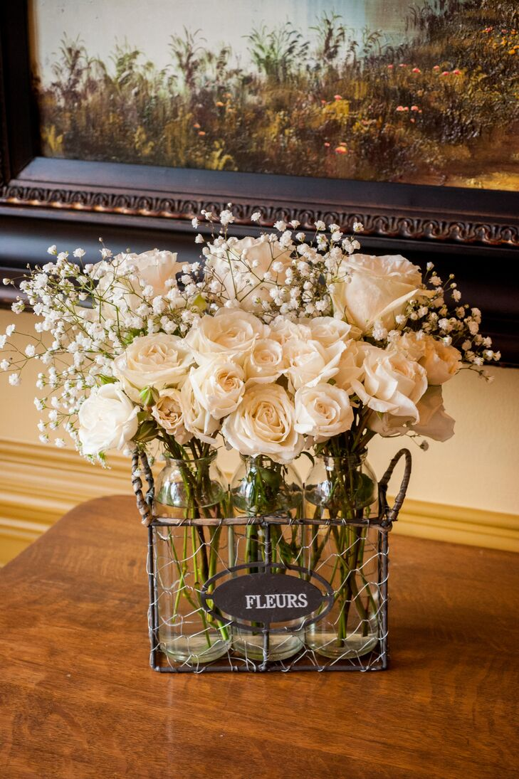 "Elegant ivory roses mixed with baby's breath inside an iron container used for decorative means, with a black-and-white sign on the front that read ""fleurs."""