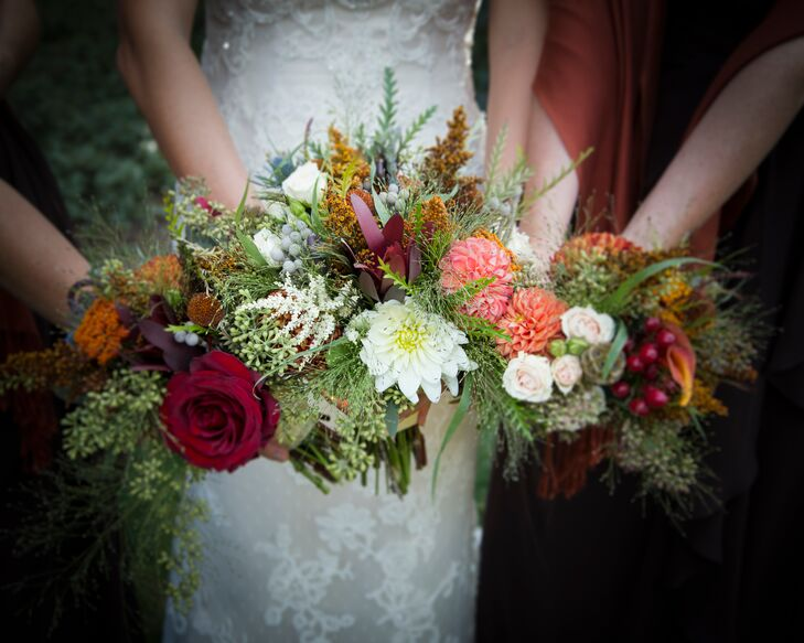 The Ruffly Rose created the bride and bridesmaids' fall-inspired bouquets including roses, dahlias, seeded eucalyptus, scabiosa pods, hypericum berries, silver brunia balls, blue thistles and astilbes. Brooklynn wanted the floral arrangements to look organic to match their rustic venue as well at the natural fall foliage.