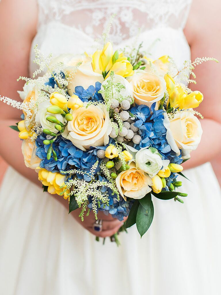 Blue and yellow wedding bouquet with ranunculus, roses, hydrangea, brunia berries and astilbes​