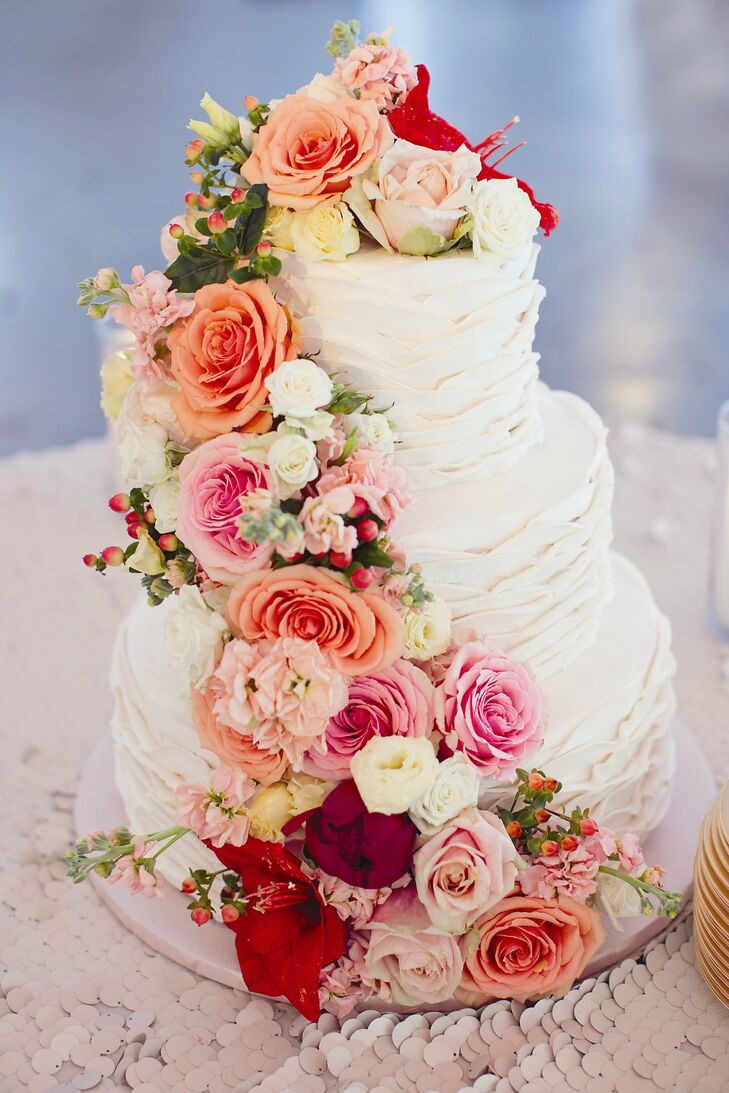 The three-tier cake featured a white ruffled, textured frosting and was decorated with fresh roses and hypericum berries.