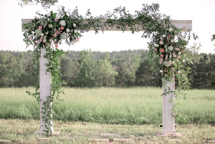 Anna and Adler had an over-the-top wooden wedding arch. It had overflowing greenery with pink and white roses, hydrangeas and lilies that enhanced the natural backdrop of rolling fields and vineyards.