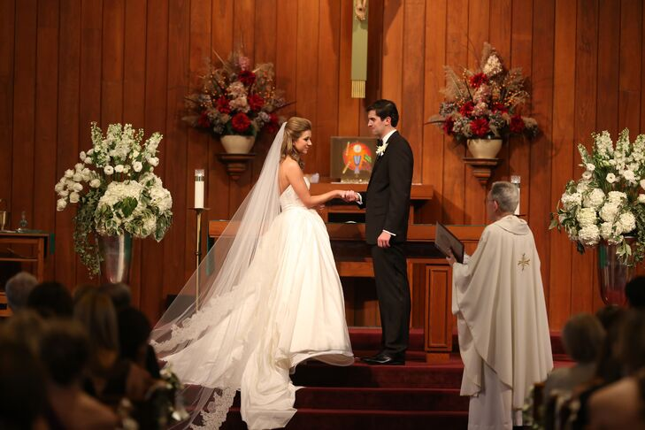 For her traditional Catholic ceremony, Kieran wore a cathedral veil with lace trim that looked beautiful with her simple ball gown. The altar at the wood-paneled church was decorated with white flower arrangements of roses, ranunculus, hydrangeas and delphiniums.
