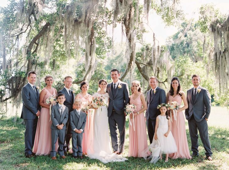 """Each bridesmaid embraced their garden-party inspiration with long Heidi dresses by J.Crew. The misty rose look had an overlapping V-neck and a pleated silk-chiffon skirt that flowed from the empire waist. """"The color was perfection with our venue's surroundings,"""" Laurie says. Their groomsmen stood beside them in these sharp charcoal and white suits from the Black Tux."""