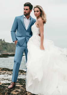 groom in blue suit and bride in ruffled wedding dress