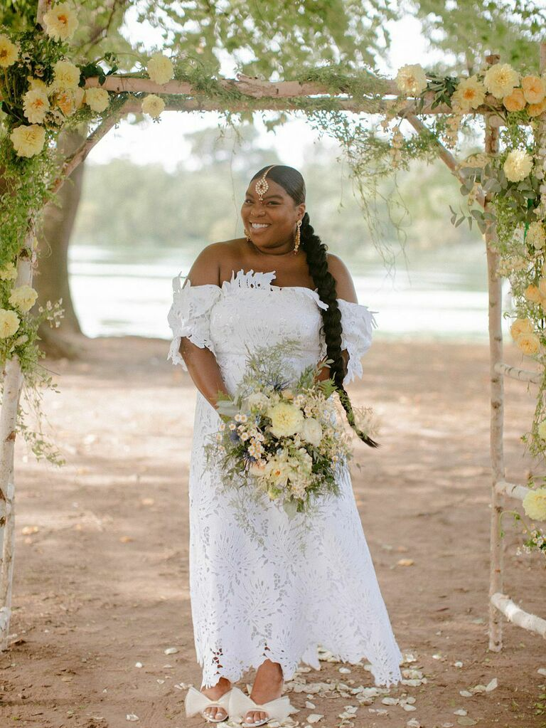 Bride holding bouquet of yellow flowers under yellow floral ceremony arch at outdoor summer wedding