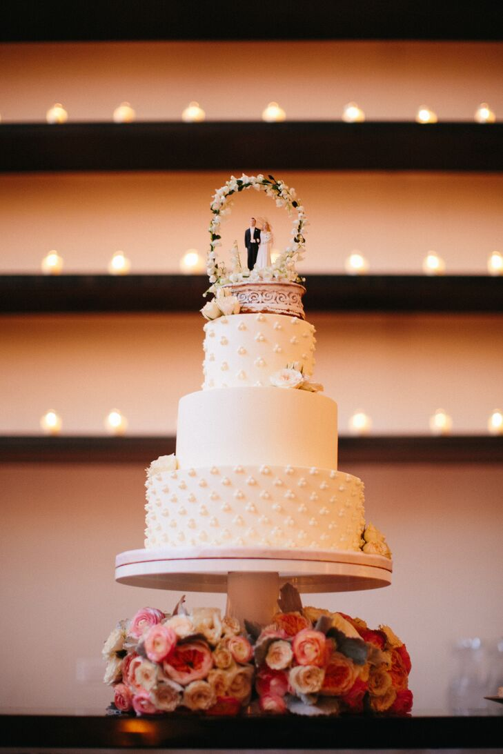 """""""We chose a carrot cake with cream cheese frosting to really emulate the taste of fall,"""" Liz says. """"Plus, it's our favorite!"""" The three-tier confection sported a delicate swiss dot piped detail as well as a cake topper that once belong to the bride's mother and grandmother. """"It's now engraved with three generations of wedding dates!"""" the bride explains."""