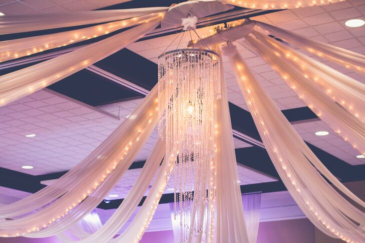 Inside the ballroom reception, the ceiling was intricately decorated with ivory linens draping from the middle of the room to the outside corners. The linens were intertwined with string lights, which shone through the fabric. A long chandelier hung in the middle of the room, with a downward spiral of crystal beads.