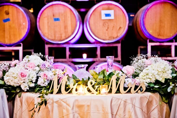 """Joanne and Rainnier took their seats at the sweetheart table, which was labeled with a gold sign that read """"Mr. & Mrs."""" The top of the table was decorated in overflowing lush pastel roses, hydrangeas and baby's breath arrangements."""
