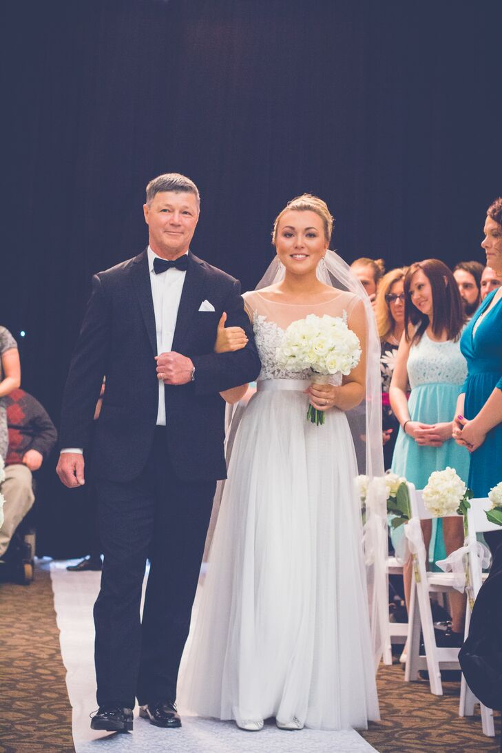 """Kyra wore an ivory wedding dress with an illusion neckline, accented bodice and a tulle skirt. """"I chose the Jacinda dress by Watters & Watters,"""" Kyra says. """"As soon as I saw this dress, I knew it was perfect. It was so comfortable and light, I was able to dance all night and feel great!"""""""