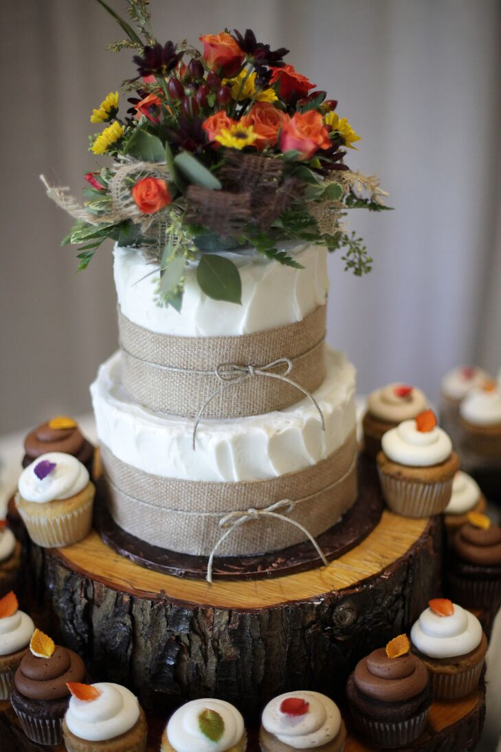 Like their rustic fall wedding florals, Ashleigh and Justin's wedding cake topper had a similar flower arrangement accented with pretty burlap bows. Each cupcake also had an edible leaf decoration.