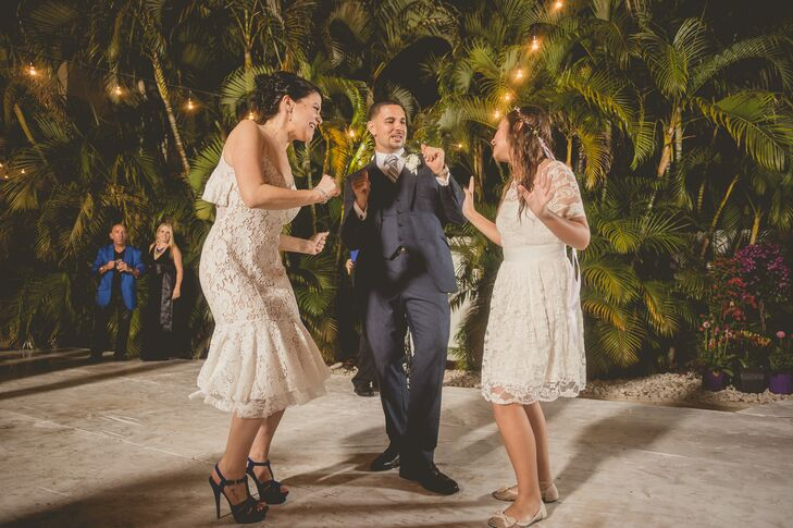 """Since heat and random rainstorms in Florida are common, Roxy knew she wanted a second dress for the reception. She picked out a tiered ivory Tracy Reese dress just to hit the dance floor in. """"It ended up being a wise choice since I got my wedding dress soaked dancing in the rain,"""" she says."""